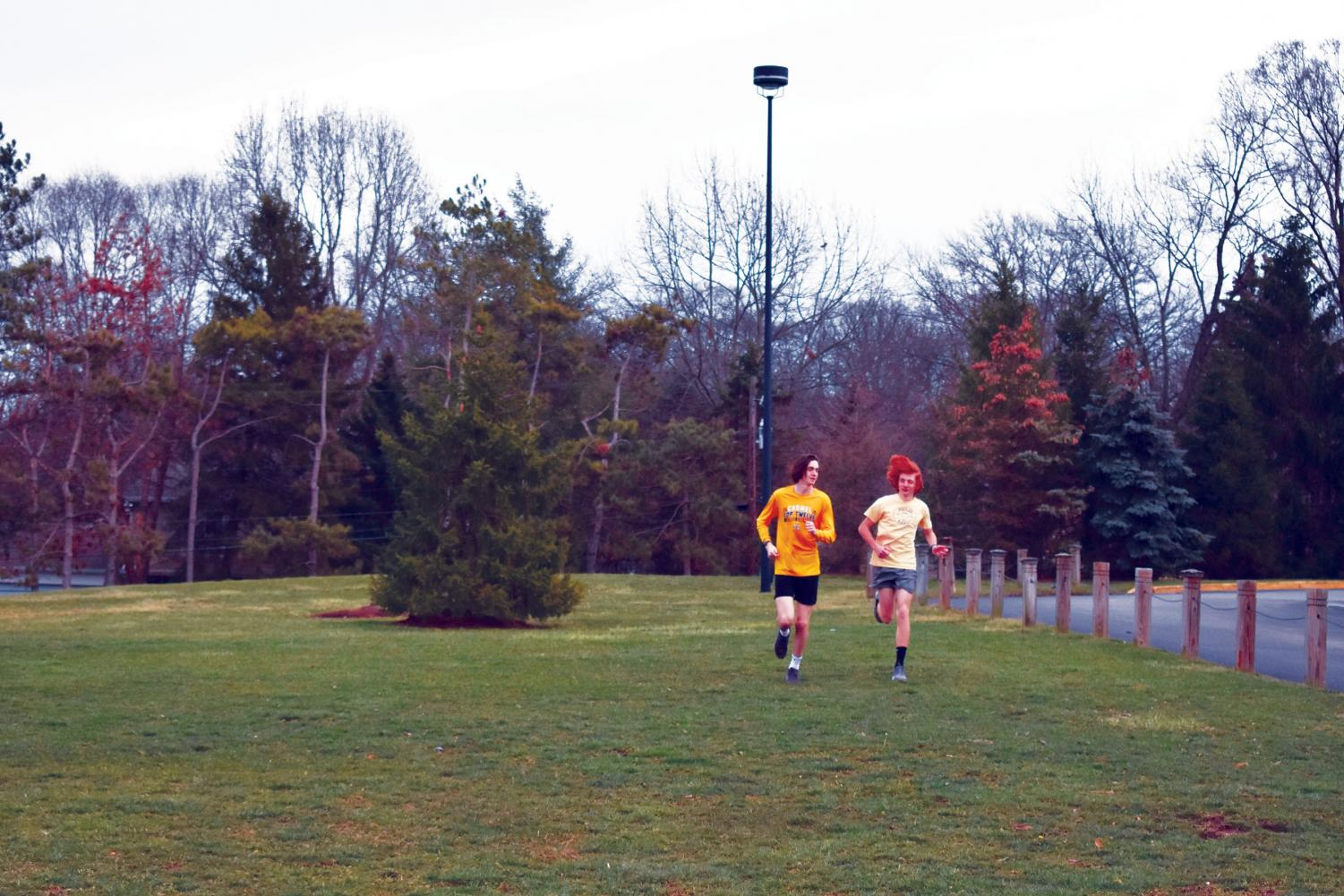 """POWER RUN: Junior Bing Hudson (left) and sophomore Charlie Schuman run laps in the field across from Murray Stadium and the Natatorium parking lot. """"We don't meet in December after a lengthy cross-country season, so the boys are excited to meet up in the locker room, run together, and get guidance from our coaches. It is a really good atmosphere that the boys build during the offseason,"""" Head Coach Colin Altevogt said."""