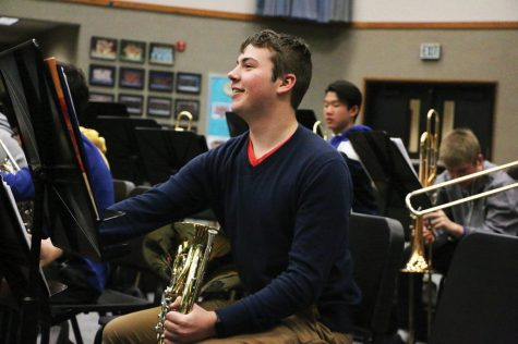 Junior Andrew (Andy) Schmidt plays around on his french horn during a break in Wind Symphony III. He said his favorite part of concert band is playing different types of music and the class helps him reenergize before the rest of his school day.