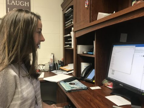 Director of Choirs Katherine Kouns reviews the lyrics to a song in her office on Jan. 17. The song was sung by Accents as part of their competition set.