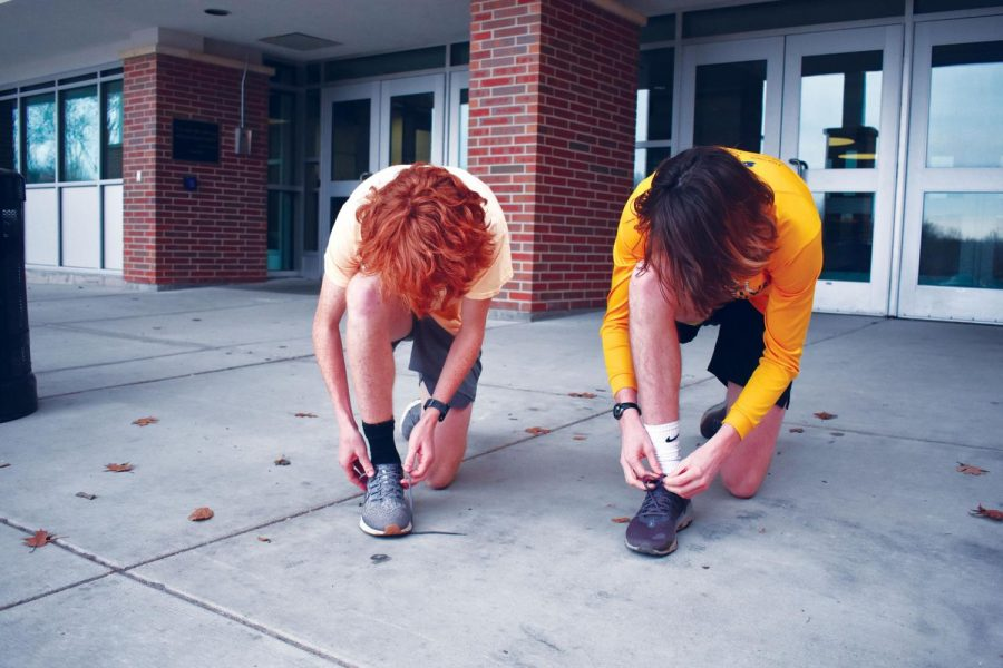 """LACING UP: Immediately after school, junior Bing Hudson (right) prepares to run with sophomore Charlie Schuman. """"I think running in the winter feels fun sometimes and exciting because the weather is really ideal for distance running,"""" Hudson said."""