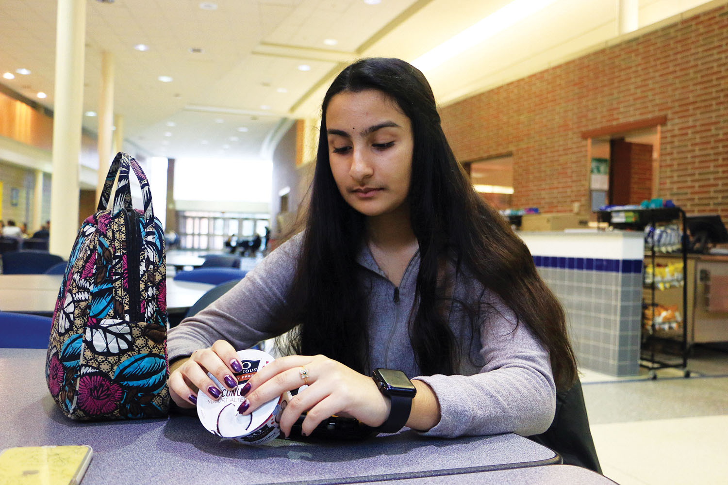 "Sophomore Yashaswini ""Yashu"" Battina looks at yogurt before she eats. She said her Type 1 diabetes diagnosis has caused her to be more aware of her diet."
