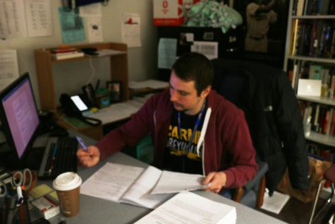 Club sponsor James Ziegler looks over assignments during passing period. According to Ziegler, Indiana-based activist Tim Bagwell will speak with the club during late February.
