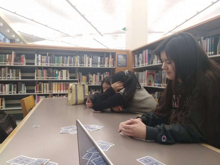 Alyssa Smith, senior and Wind Symphony I member, plays cards in the library during her release period. Smith said she is looking forward to performing at CBDNA.
