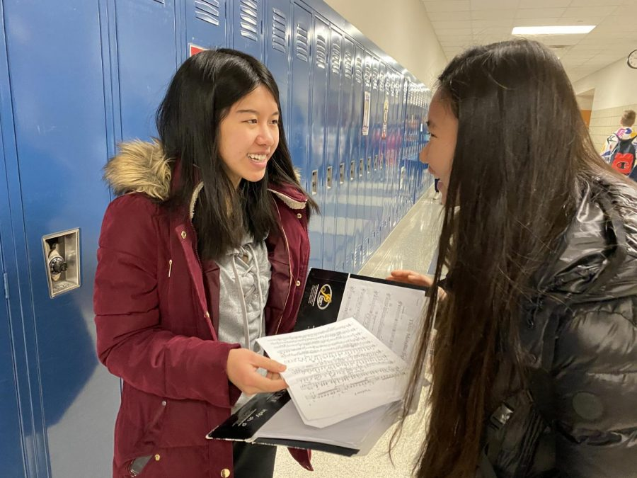 Chloe Chui (left), member of Symphony Orchestra and junior, looks over her music with Alia Rumreich (right), member of Symphony Orchestra and junior. Chui said the Symphony Orchestra has been focusing heavily on intonation and transitioning back to regular classes after their chamber music unit.