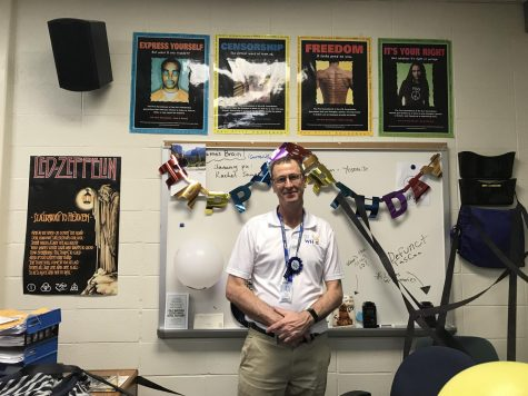 Radio adviser Dominic James stands at his desk on his 60th birthday. WHJE staff members decorated his classroom and the radio hallway for the occasion.