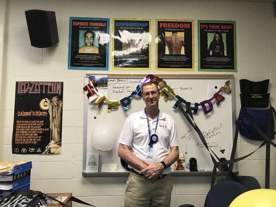 Radio+adviser+Dominic+James+stands+at+his+desk+on+his+60th+birthday.+WHJE+staff+members+decorated+his+classroom+and+the+radio+hallway+for+the+occasion.