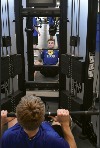 HEAVY LIFTING:  Clay Stirsman, member of the men's golf team and senior, lifts weights during pre-season practice. Stirsman said golf has evolved from being distance driven to having more emphasis on power and athletics to be more successful at certain skills.