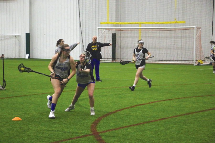 "MAKING MOVES: Lacrosse Head Coach Brandon Burke gives orders to senior Caroline Ramsey as she navigates her way through her teammate during practice on Saturday morning.  ""You get to a point where you're having to do so many things that you get so exhausted that making decisions is hard,"" Ramsey said."