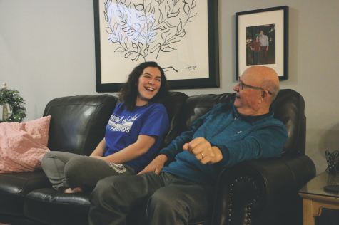 Junior Isabel Jensen and her grandfather watch a music video together for a TikTok. Jensen said she thinks her videos went viral because they involve interacting with other people, which is a heartwarming experience.