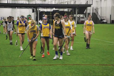 SISTERHOOD: Caroline Ramsey, varsity lacrosse player and senior, walks off the field with her teammates. Ramsey, as well as swimming Head Coach Chris Plumb, said positive and uplifting team atmosphere motivates athletes to keep playing their sport.