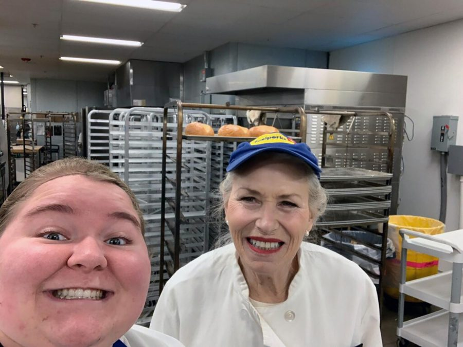 Senior Mia Bassett (left) takes a picture in the bakery at Market District. Bassett said that it has been so busy lately that she has had to bag groceries as well.