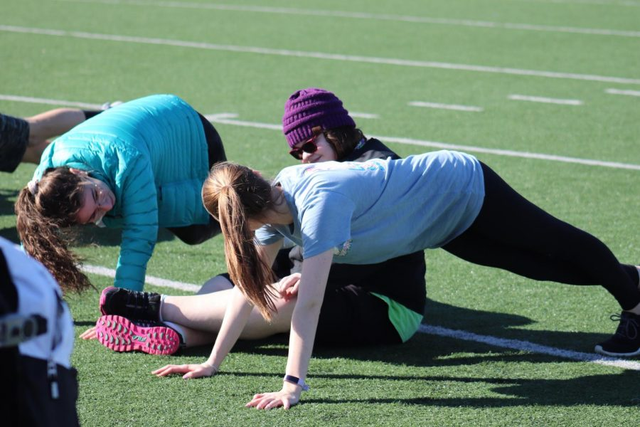 Maddy Paxton, Unified Track member and senior, stretches with her teammates before practice.