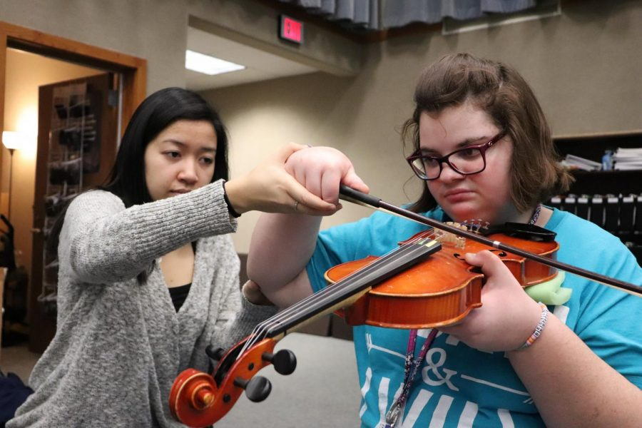 Linh Nguyen, United Sound mentor and senior,  helps Maddy Paxton, United Sound member and senior, play an instrument at a United Sound meeting.