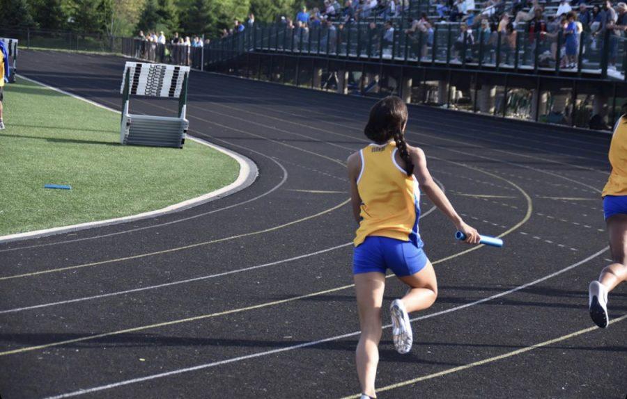 Reagan Smiley, women's track runner and senior, runs a relay at a meet last season. Smiley said she has run since fourth grade.