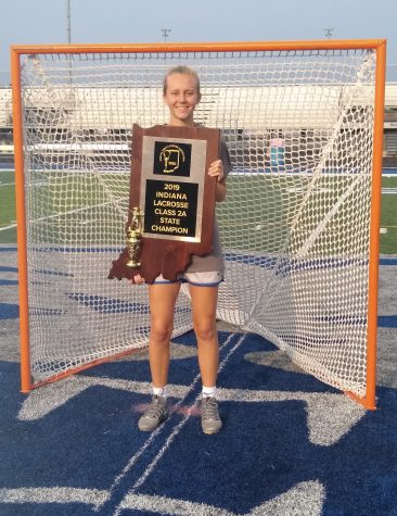 Jillian Schlieper, women's lacrosse player and senior, poses with the State trophy after the game last season. Schlieper said she was disappointed that the spring season was cut short since she was hoping to win three straight State titles in a row.