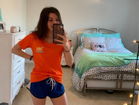 Sophomore Grace Hutton poses in her Goldfish Swim School shirt. Hutton served as a swim teacher at the school until it temporarily closed following the stay-at-home order due to COVID-19.