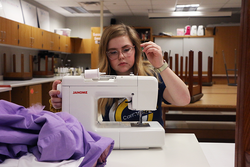 "Junior Marissa Cheslock threads her sewing machine. When determining when do repurpose clothes or start from scratch, she said, ""If it"