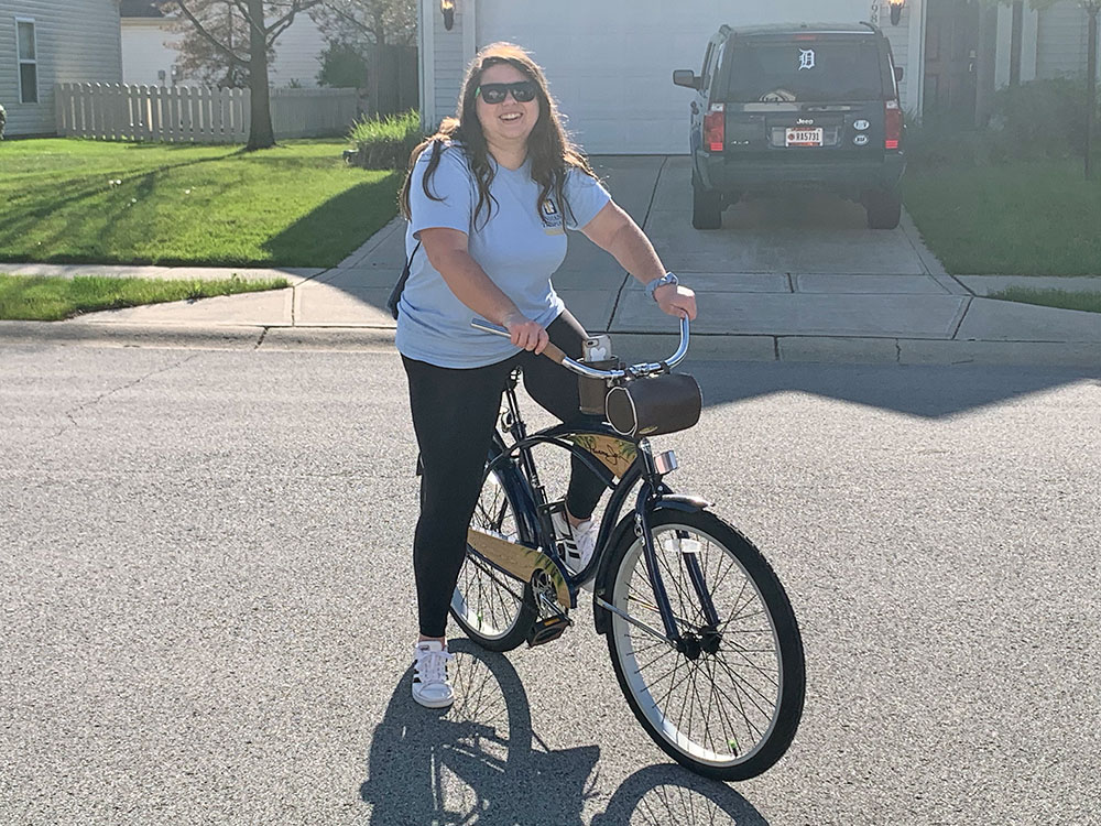 Senior Stephanie Morton stands on her bike before going on a bike ride with her friends. She said riding her bike has been a good way to socially distance with her friends while remaining active.