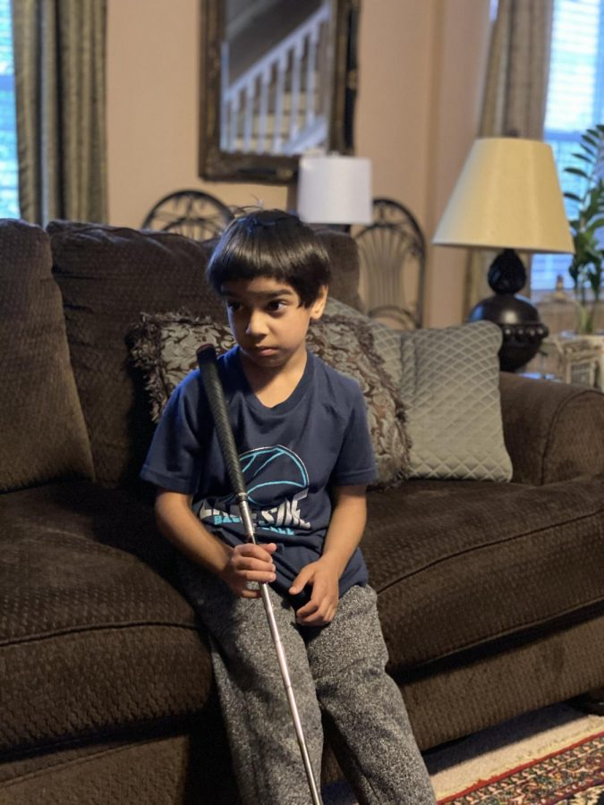 Upset at his older sister for ruining his golf shot, first grader Zaid Idrees looks on with an unhappy expression, standing in his living room on May 11, 2020. Zaid did not win the golf game. Because of quarantine, the Idrees family often plays their own version of indoor golf, setting up targets in the living room to hit golf balls at. Despite losing the game, Zaid says that he likes playing indoor golf with his family because it's fun.