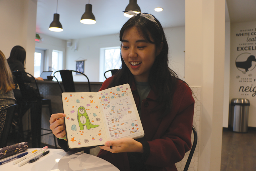 Senior Jaehee Kim shows her friends a spread in her bullet journal. Kim said she likes to make paper crafts and prefers to decorate her bullet journal with paper rather than calligraphy.