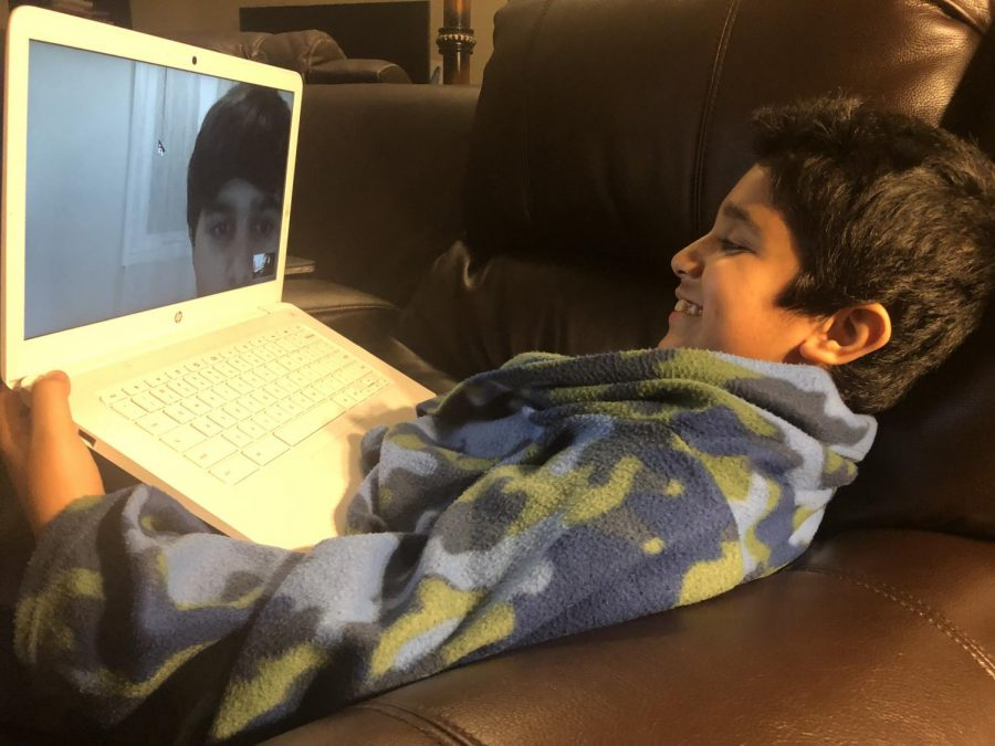 """My brother and third grade student Ayan Kalra lounges on the sofa at his home in Carmel as he talks to his cousins Dhruv Chawla and Dhairya Chawla, who are in Mississauga, Ontario, over Google Hangouts on May 11, 2020. Google Hangouts and other video conference apps have increased in popularity during the COVID-19 pandemic as the tolls of social distancing on social life became more evident. """"Software like Hangouts helped me connect more with my family during this traumatic time, and gave me a deeper sense of emotional connection during this time,"""" Ayan said."""