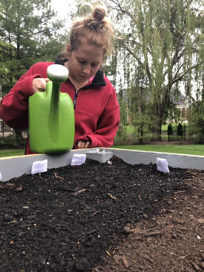 """Elyse Reed stands in her backyard holding a watering can as she tends to her plants on May 10, 2020. She planted the various vegetable seeds in her gardening box a couple days earlier. """"It's a fun and creative way to spend my time these days and I am excited to see how they turn out,"""" Reed said."""