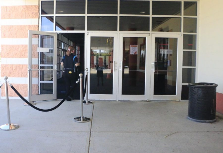Employees set up Regal's new front door leading to a sticker filled box office to mark six feet distances This is one of the many newly implanted rules and guidelines to keep the theater open.