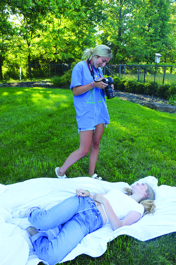 Senior Chloe Eades takes a photo of her friend, Linnea, as she poses on the ground for a portrait. Eades said taking photos of her friends is one of the ways she helps her friends see themselves in a more positive way.