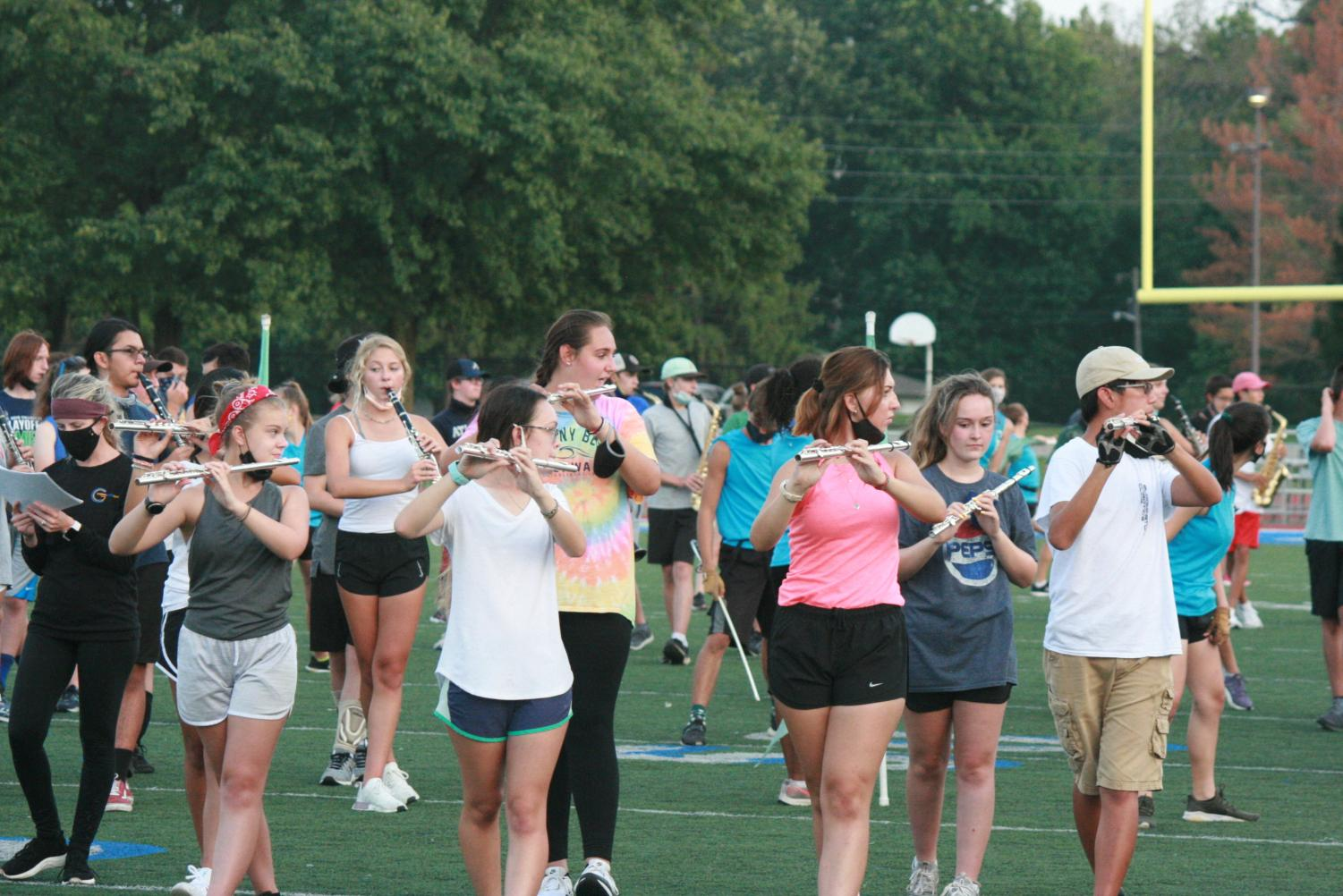 The flute section moves in formation together during rehearsal. They practice their music and the moves at the same time, putting it together with the rest of the band. Social distancing is enforced as much as possible.