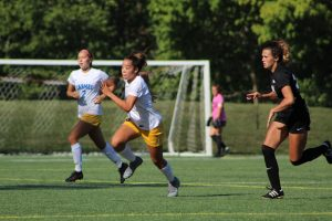 (MIDDLE) Saliyah Brady, women's varsity soccer team member and junior, runs for a ball during one of her soccer games. Brady said she shows her support for the Black Lives Matter (BLM) movement via attending protests rather than in her sport and hopes her actions and protests push for reforms and more accountability in police departments around the nation.