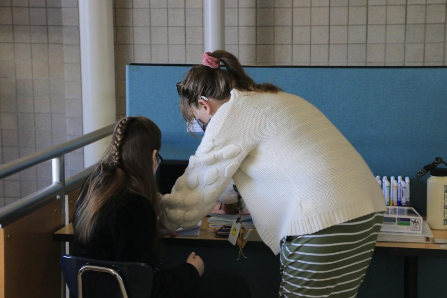 HELPING HANDS: Special Education instructor Andie Olson aides senior Megan Hennesey in her math class on March 3. Hennesey worked on developing division skills and giving counting exact change with Mrs. Olson.