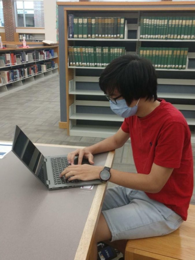 Noah Tan, Science Bowl president and senior, sits in the CHS library during school. According to Tan, Science Bowl will mainly function virtually this year due to COVID-19.