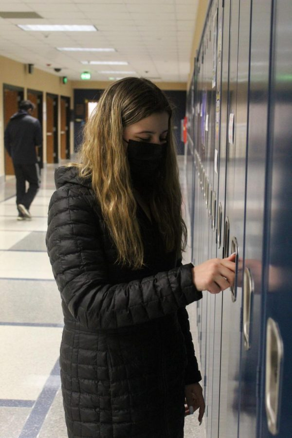 PASSING PERIOD PASTIME: Lizzie Maurer, Algebra II student and junior, opens her locker to get a textbook before class on Feb. 12. Maurer said she enjoys Algebra II as it is a good balance between a hard and fun class.