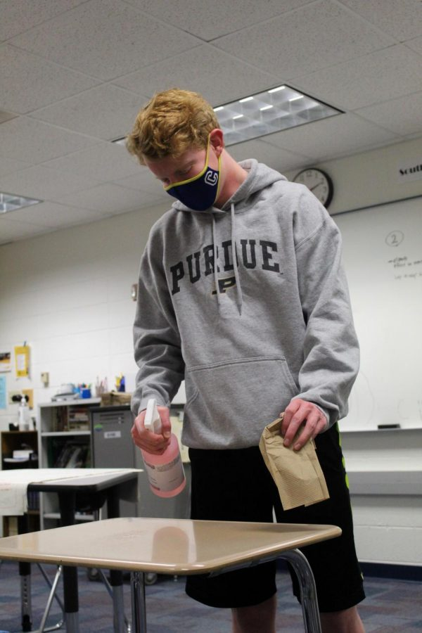 SUPER SANITATION  Graham Seaver, AP seminar student and junior, cleans his desk prior to the start of class on March 11. Seaver said he cleans his desk before and after class to ensure that everything is safe for him to use.