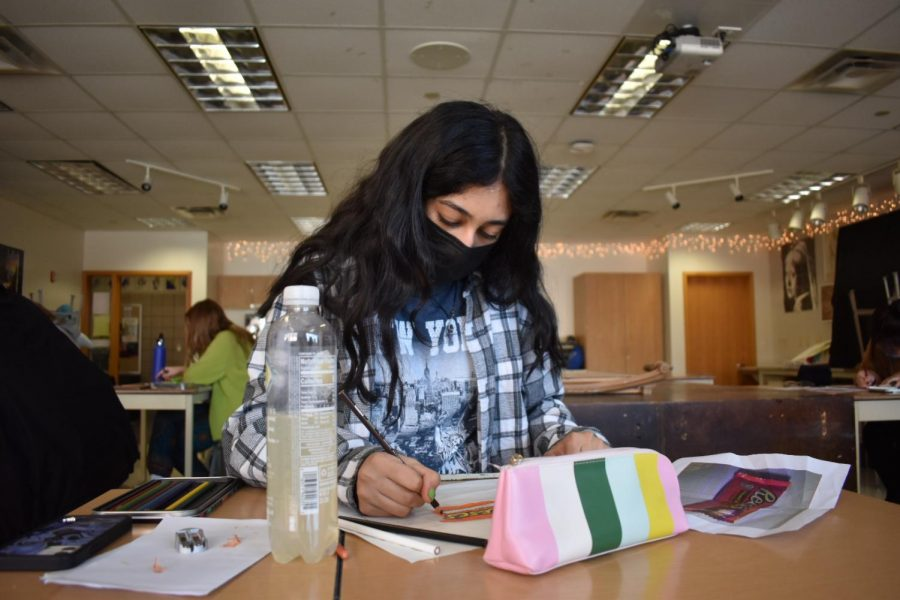 FINISHING TOUCHES: Freshman Sanya Gopalani adds color to her art project on Feb. 24. The Drawing 2 class had most recently been creating colored pencil drawings of candy, and Gopalani had chosen to draw Reese's Cups.