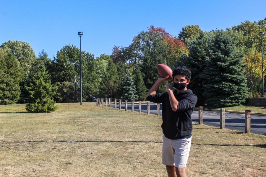 Freshman Shravan Chengalva throws a football outside for fun. He said fantasy football has changed the way he watches real football, including his interest in different teams.