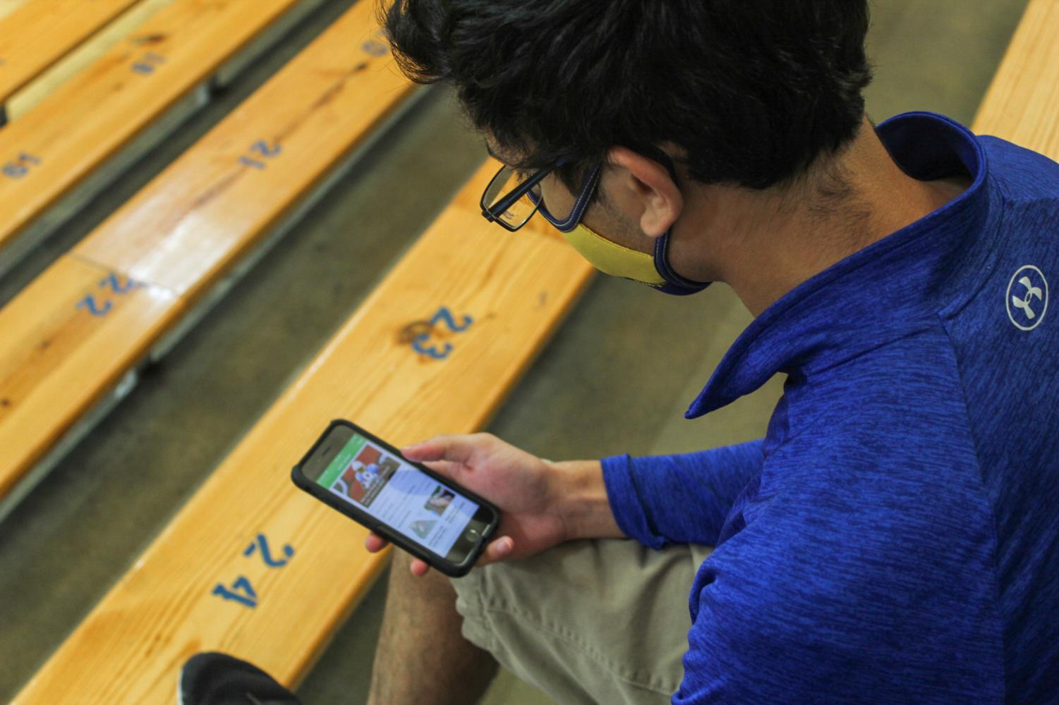 Senior Neal Joshi plays fantasy football on his phone while sitting in the varsity gym. Fantasy football has greatly increased popularity over the past few years and has caused more interest in the NFL.