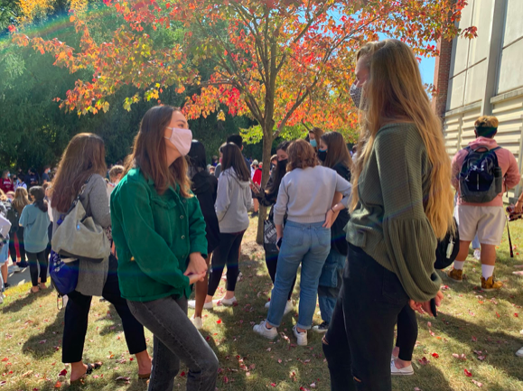 Student body president Julia Heath talks to a friend while waiting outside after the fire alarms went off on Oct. 7. She said she is excited to celebrate the hard work of the administration and bus staff this week and next week.