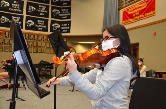 Rachel Wu, member of Symphony Orchestra and sophomore, plays a piece during after-school rehearsal. Wu said she is excited to perform under different circumstances for the fall concert this year.