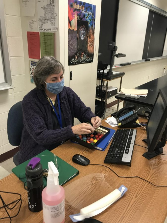 Science Bowl head sponsor Virginia Kundrat sits at her desk and plays with a science model. She sponsors the Science Bowl team, which is preparing for an invitational competition in January.
