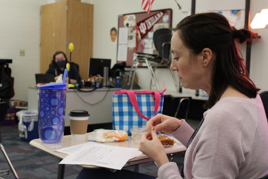 English 11 teacher Emily LeFors eats lunch while looking over paper during a meeting discussing changes to the english curriculum for the 2020-2021 school year to find adaptations for hybrid schedules. LeFors took her mask off to enjoy her lunch.