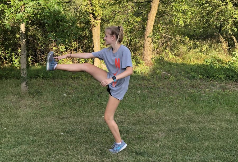 Savannah Hill, cross-country runner and senior, stretches after practice. Hill said she feels that summer practices have prepared the team well for the season.