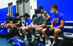 MASKS ON:  Members of the wrestling team put on their gear before practice. Harel Halevi, varsity wrestler and senior, said he believes contracting the virus while wrestling is less likely than it seems because athletes meet only a few people at each meet on top of the many new safety procedures.