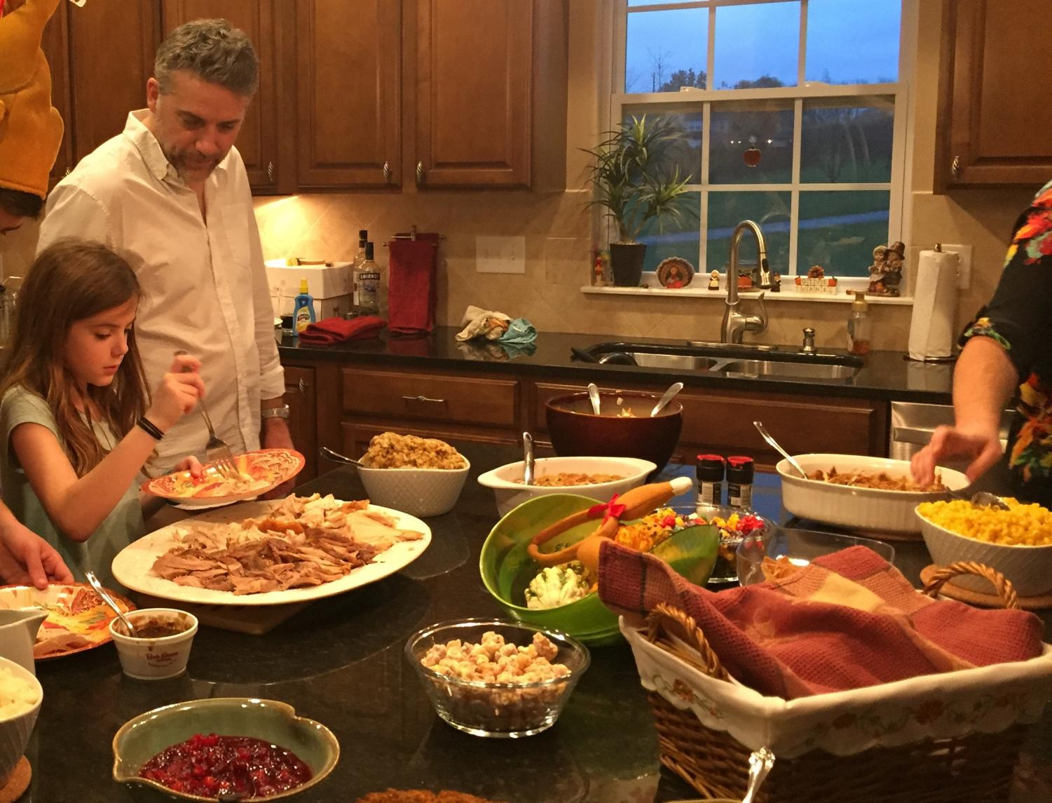 """In 2016, freshman Ava Beckman and her father, David Beckman, collect food from the kitchen counter on Thanksgiving. Beckman said her family normally celebrates Thanksgiving with many family members, but this year, due to the coronavirus, will most likely only celebrate Thanksgiving with immediate family. Beckman said, """"I would say just go ahead and make those changes to be safe. It's better to be safe than sorry. I'd say you would rather have a smaller Thanksgiving celebration and not have anybody get sick, instead of having a big celebration and then half those people have COVID and it's a very dangerous virus, somebody could be in the hospital, somebody could pass away."""""""