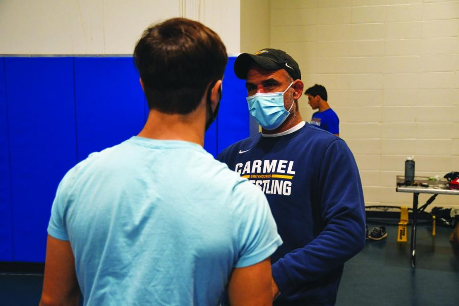 SAFE PRACTICE:  Wrestling head coach Ed Pendoski tells an athlete what to work on during practice. According to Pendoski, he reminds his athletes to stay safe as well as optimistic even when practices might not be ideal.