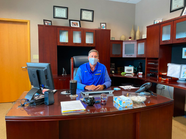 Principal Tom Harmas sits at his desk while wearing a mask to comply with COVID-19 guidelines. He said that although the colder weather will make it harder for certain activities to take place, he still thinks this school's plan to combat the effects of the pandemic will be successful in the winter.