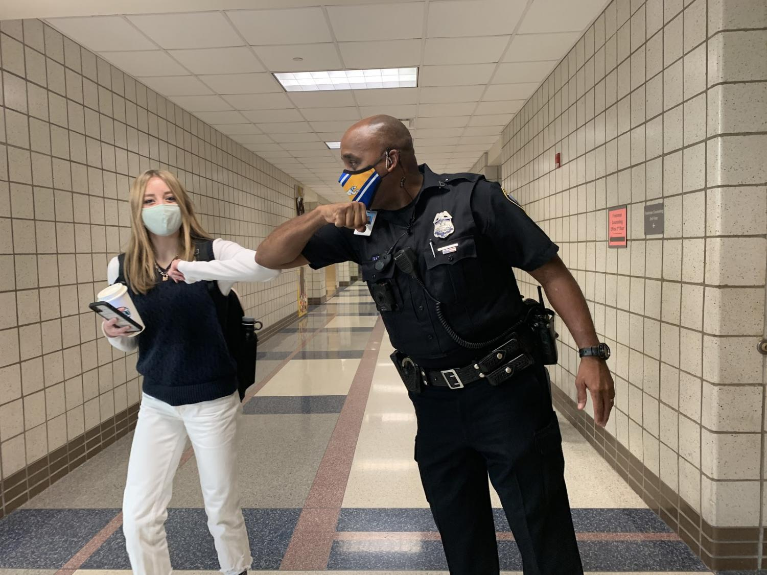 Officer Scott Moore greets a student in the hallways. Moore said he tries to be in the hallways every passing period.