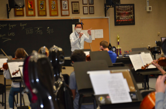 Director of Orchestras Thomas Chen conducts the Carmel Symphony Orchestra during after-school rehearsal. Chen said all of the precautions such as  physical distancing, wearing masks, and disinfecting are in place during rehearsal.