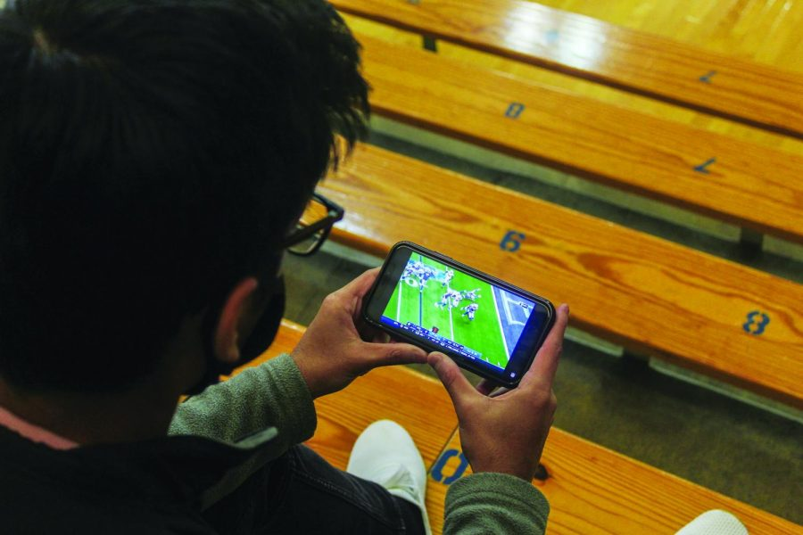 Junior Shrithan Sandadi streams a football game on his phone during school. Sandadi said he only streams games on his phone when conventional games are not being shown on TV channels.