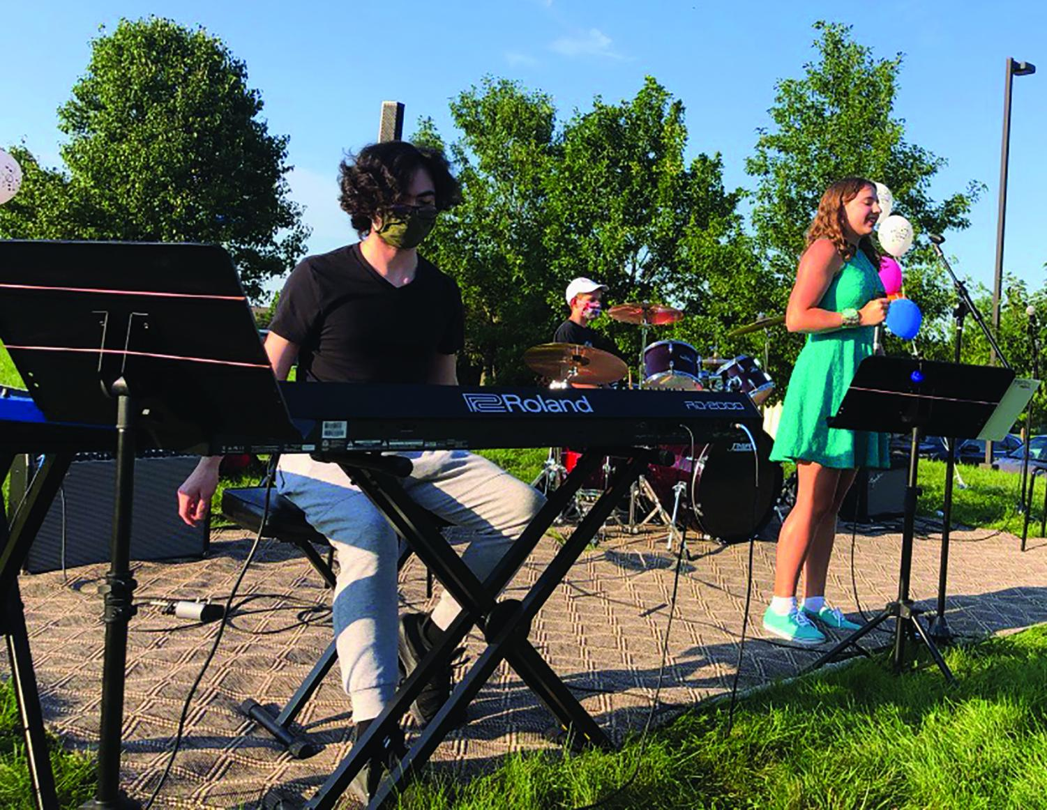 """Mackenzie Edwards (right), lead singer of band """"Lightning in a Bottle"""" and sophomore, sings outside with accompaniment from her bandmates. Edwards said that being involved with the band has allowed her to interact with a vibrant community and share music with others."""
